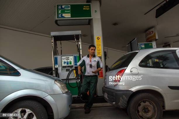 An attendant prepares to refuel an automobile at a Petrobras Distribuidora SA gas station in Sao Paulo Brazil on Monday Dec 11 2017 Petroleo...