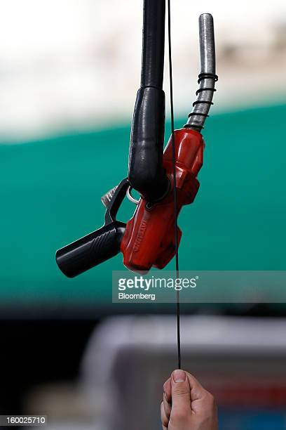 An attendant pulls a fuel pump to fill up a vehicle at a gas station in Tokyo Japan on Friday Jan 25 2013 Japan's consumer prices fell for the...