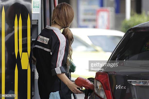 An attendant refuels a customer's vehicle at an Idemitsu Kosan Co gasoline station in Tokyo Japan on Friday Aug 12 2016 At an Idemitsu shareholder...