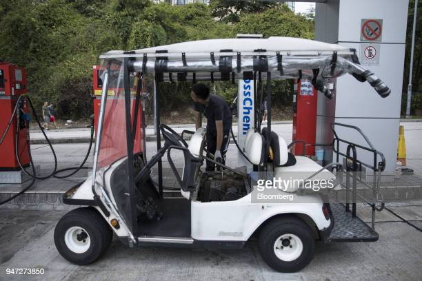 An attendant refuels a golf cart at a gas station in Discovery Bay a residential project developed by Hong Kong Resort Co on Lantau Island in Hong...