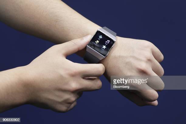 An attendant shows a Fitbit Inc Ionic smartwatch for a photograph at the Wearable Expo in Tokyo Japan on Thursday Jan 18 2018 The trade show...