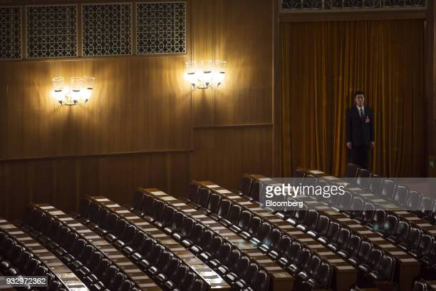 An attendant stand inside the Great Hall of the People ahead of a session during the first session of the 13th National People's Congress in Beijing...