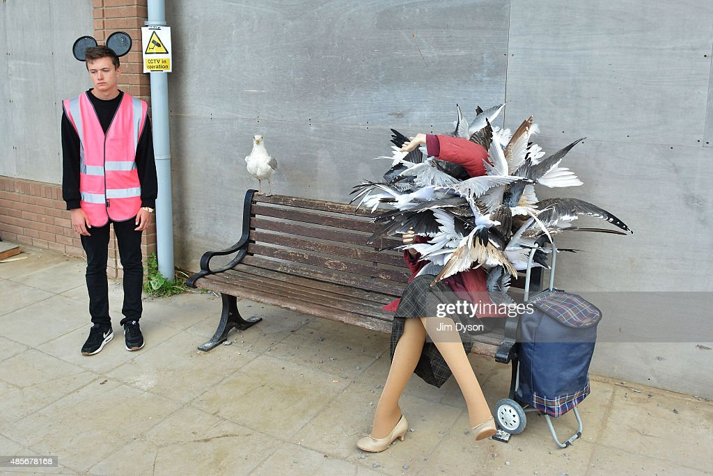 An attendant stands beside a sculpture by Banksy depicting a woman being attacked by seagulls, as Banksy's Dismaland Bemusement Park opens to the public, on August 28, 2015 in Weston-Super-Mare, England. Graffiti artist Banksy has opened the subversive, pop-up theme park styled exhibition at the derelict seafront Tropicana lido, featuring the work of 50 artists. The 'Bemusement Park' combines dark humour and 'entry-level anarchism' and will open for just five weeks.