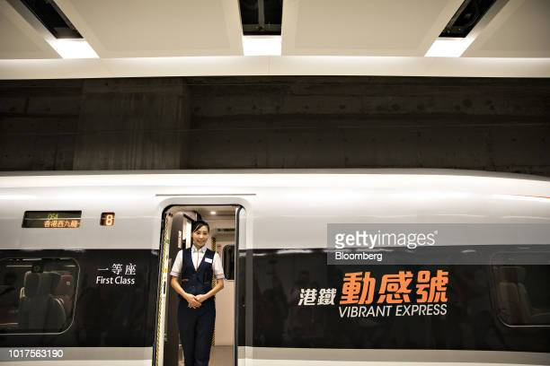 An attendant stands for photographs at a door of a GuangzhouShenzhenHong Kong Express Rail Link train sitting on a platform at the West Kowloon...