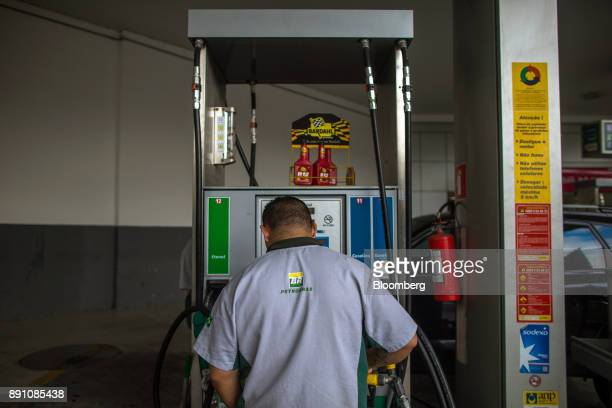 An attendant stands in front of a fuel pump at a Petrobras Distribuidora SA gas station in Sao Paulo Brazil on Monday Dec 11 2017 Petroleo Brasileiro...