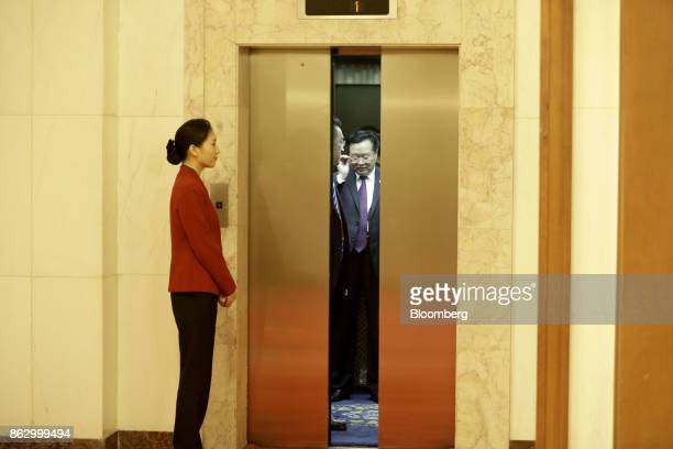 An attendant stands near a lift as delegates arrive at the Great Hall of the People during the 19th National Congress of the Communist Party of China...