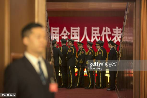 An attendant stands next to a door as members of the People's Liberation Army band walk inside the Great Hall of the People ahead of the opening of...