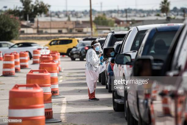 An attendant talks to a person waiting in their car at a coronavirus testing site at Ascarate Park on October 31, 2020 in El Paso, Texas. As El Paso...