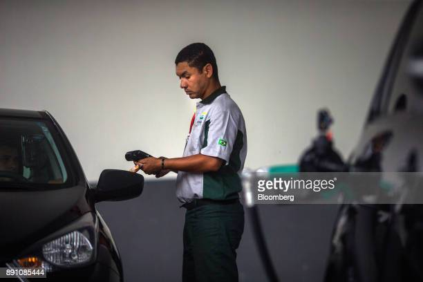 An attendant uses a credit card reader to charge a customer for fuel at a Petrobras Distribuidora SA gas station in Sao Paulo Brazil on Monday Dec 11...