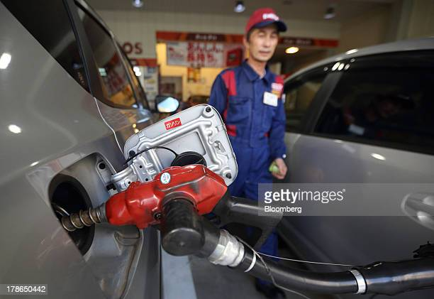 An attendant walks near a vehicle being refueled at a gas station in Tokyo Japan on Friday Aug 30 2013 Japan's consumer prices increased at the...