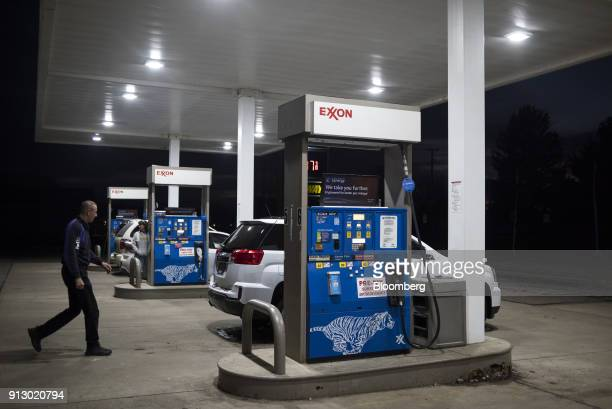 An attendant walks towards a vehicle in front of fuel pump at an Exxon Mobil Corp gas station in Nashport Ohio US on Friday Jan 26 2018 Exxon Mobil...