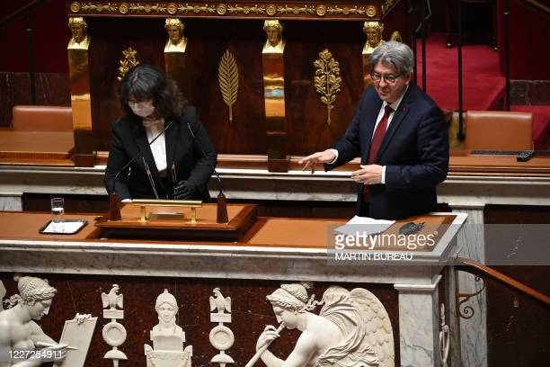 An attendant wearing a face mask and protective gloves cleans the microphones as French leftist party La France Insoumise's leader Jean-Luc Melenchon...