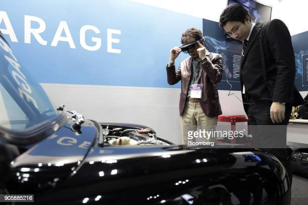 An attendant wearing a pair of Microsoft Corp HoloLens mixed reality smartglasses left tries out Yamagata Corp's HoloGarage vehicle maintenance AR...