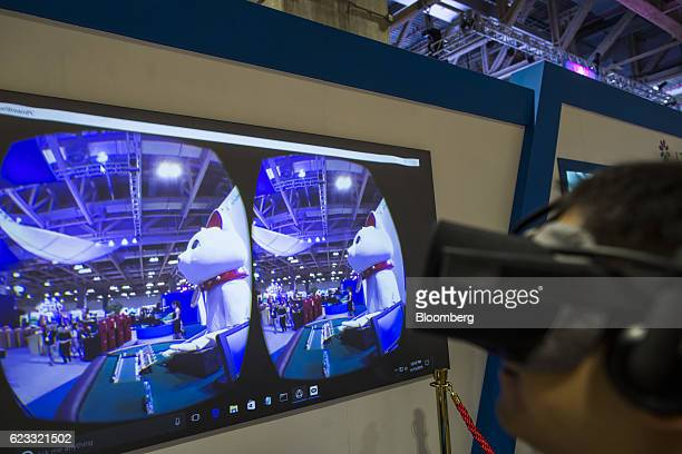 An attendant wears an Oculus VR Inc headset as a screen displays an LT Game Ltd ADV1 electronic croupier in the likeness of a cat during a...
