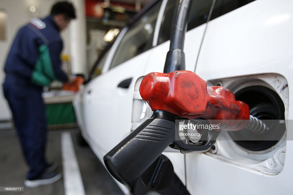 An attendant wipes the mirror of a vehicle as a fuel pump fills the tank at a gas station in Tokyo, Japan, on Friday, Jan. 25, 2013. Japan's consumer prices fell for the seventh time in eight months, underscoring the risk that the central bank may struggle to reach a 2 percent inflation target unless it implements new easing measures earlier than planned. Photographer: Kiyoshi Ota/Bloomberg via Getty Images
