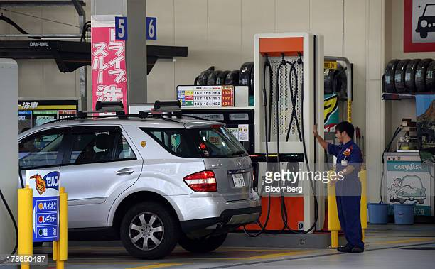 An attendant works near a vehicle at a gas station in Tokyo Japan on Friday Aug 30 2013 Japan's consumer prices increased at the fastest pace since...