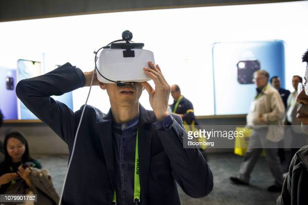 An attendee adjusts a headset to play the Huawei VR2 virtual reality music game at the Huawei Technologies Co booth at the 2019 Consumer Electronics...