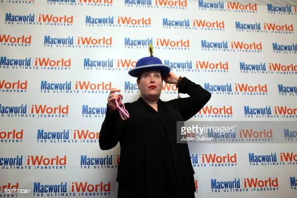 An attendee adjusts her hat as she stands in a photo booth during the Macworld iWorld Expo at the Moscone Convention Center on January 26, 2012 in...