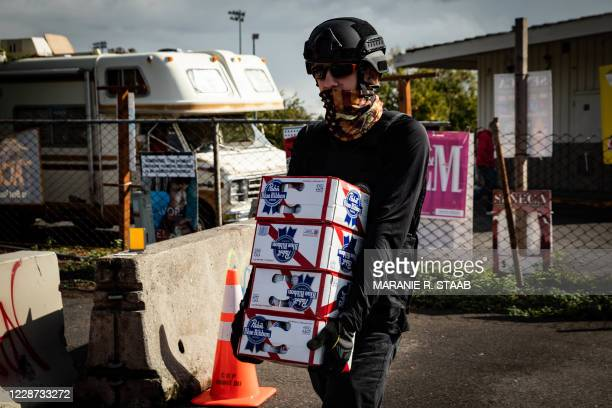 An attendee at a Proud Boy rally carries beer into Delta Park before organizers begin to speak in Portland, Oregon on September 26, 2020. - Far-right...