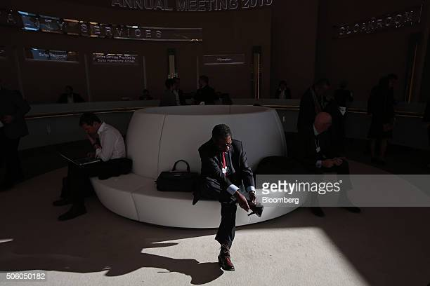 An attendee attaches anti slip snow grips to the soles of his shoes between sessions at the World Economic Forum in Davos Switzerland on Thursday Jan...