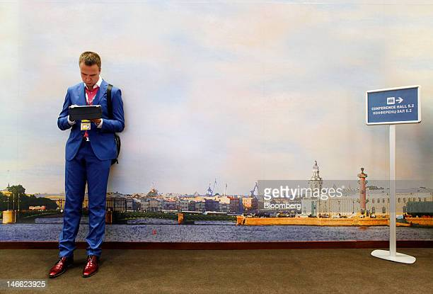 An attendee checks his Apple Inc iPad as he waits for a conference session to start on day one of the Saint Petersburg International Economic Forum...