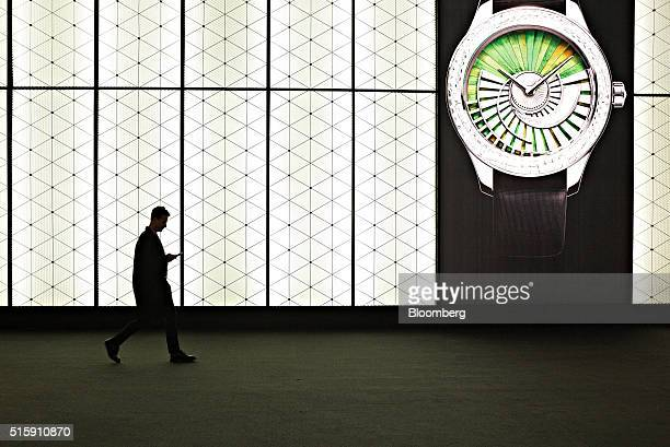 An attendee checks his mobile device during the 2016 Baselworld luxury watch and jewelry fair in Basel Switzerland on Wednesday March 16 2016 1500...