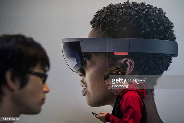An attendee checks his mobile phone while standing next to a poster of a model wearing the Microsoft Corp HoloLens augmented reality viewer at the...