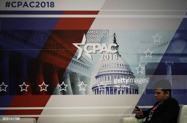An attendee checks his phone in front of a CPAC 2018 sign during CPAC 2018 February 22 2018 in National Harbor Maryland The American Conservative...