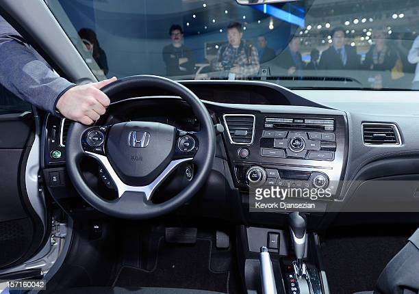 An attendee checks the steering wheel of new 2013 Honda Civic sedan during the Los Angeles Auto show on November 29, 2012 in Los Angeles, California....