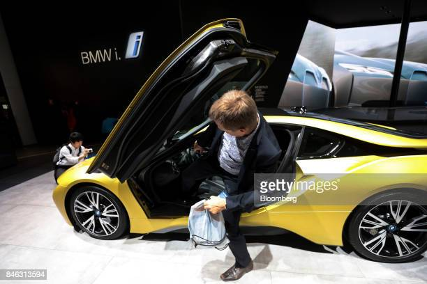 An attendee climbs out from the butterfly doors of a BMW i8 electric automobile manufactured by Bayerische Motoren Werke AG on the first media...