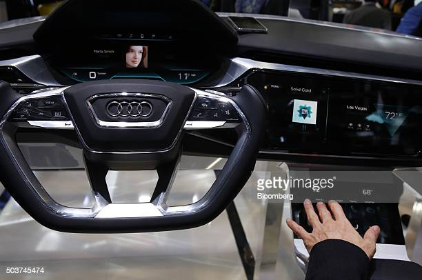 An attendee demonstrates the dashboard for the Audi AG ETron Quattro Concept vehicle during the 2016 Consumer Electronics Show in Las Vegas Nevada US...