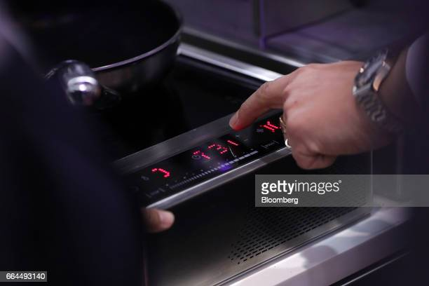 An attendee demonstrates the operation of a flight safe cooking system by Lufthansa Technik AG at the Aircraft Interiors Expo in Hamburg, Germany, on...