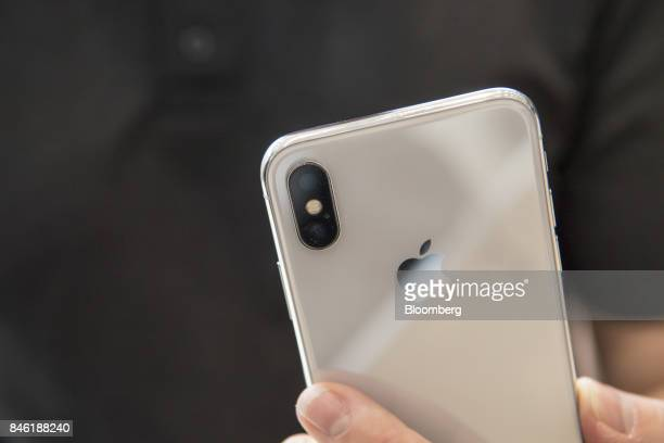 An attendee displays an Apple Inc iPhone X for a photograph during an event at the Steve Jobs Theater in Cupertino California US on Tuesday Sept 12...