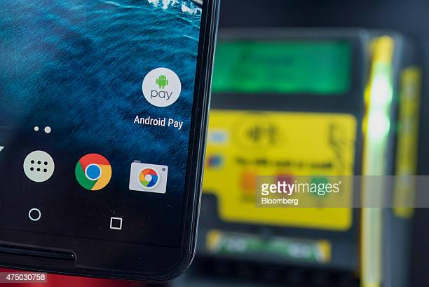 An attendee displays Google Inc Android Pay icon on a mobile device for a photograph during the Google I/O Annual Developers Conference in San...