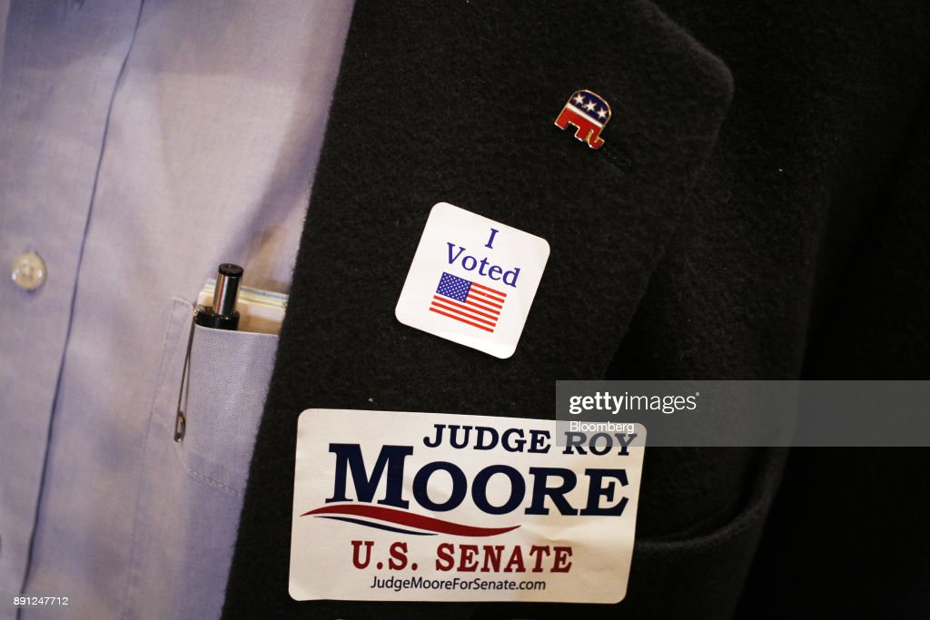 An attendee displays stickers on his jacket during an election night party for Roy Moore, Republican candidate for U.S. Senate from Alabama, in Montgomery, Alabama, U.S., on Tuesday, Dec. 12, 2017. Alabama's U.S. Senate race should have been an easy victory for a Republican candidate in a state that hasn't sent a Democrat to the chamber in a generation and overwhelmingly backed President Donald Trump in last year's election. Photographer: Luke Sharrett/Bloomberg via Getty Images