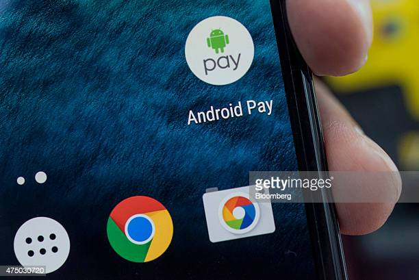 An attendee displays the Google Inc Android Pay icon on a mobile device for a photograph during the Google I/O Annual Developers Conference in San...