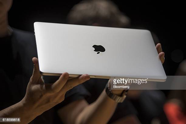 An attendee displays the new MacBook Pro laptop computer during an event at Apple Inc headquarters in Cupertino California US on Thursday Oct 27 2016...
