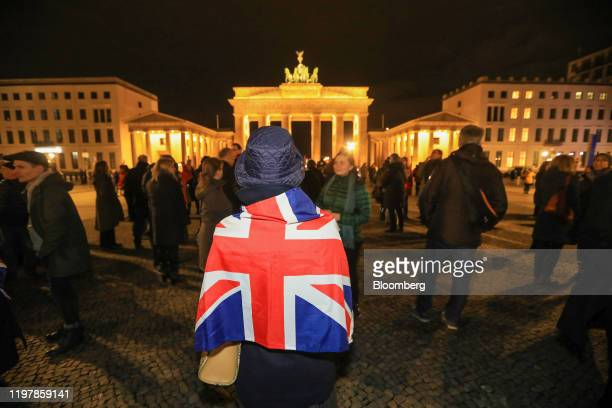 An attendee draped in a British national Union flag also known as a Union Jack during a flashmob gathering at Brandenburg Gate to sing the Anthem of...