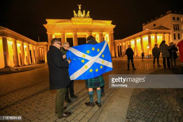 An attendee draped in a Scottish national flag, adapted to with the stars of the European Union, attends a gathering at Brandenburg Gate, to sing the...