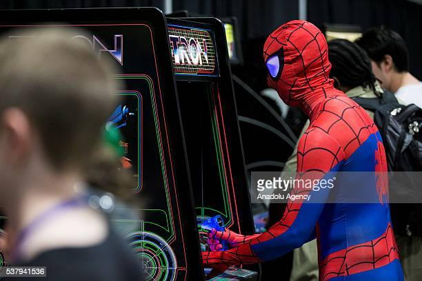 An attendee dressed as SpiderMan plays an original Tron arcade cabinet at Awesome Con which is being held at the Washington Convention Center from...