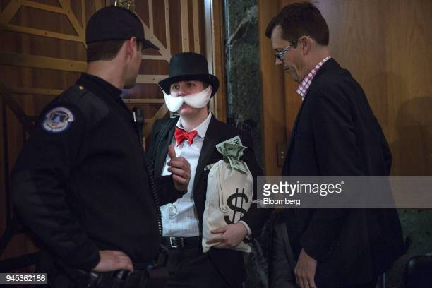 An attendee dressed as the 'Monopoly Man' exits a Senate Banking Housing Urban Affairs Committee hearing with Mick Mulvaney acting director of the...