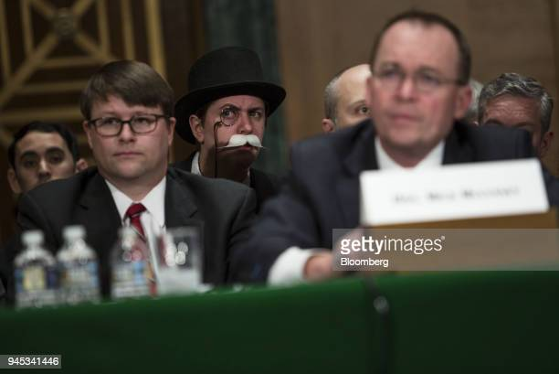 An attendee dressed as the 'Monopoly Man' listens during a Senate Banking Housing Urban Affairs Committee hearing with Mick Mulvaney acting director...