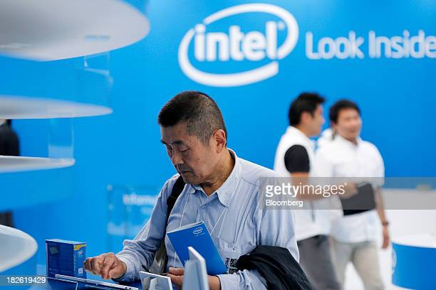 An attendee examines a device at the Intel Corp booth at the CEATEC Japan 2013 exhibition in Chiba City Japan on Tuesday Oct 1 2013 CEATEC an...