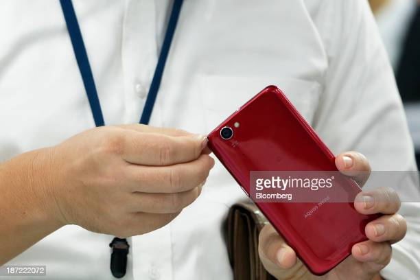 An attendee examines a Sharp Corp Aquos Phone Zeta SH01F smartphone for NTT Docomo Inc that features the indium gallium zinc oxide display during a...