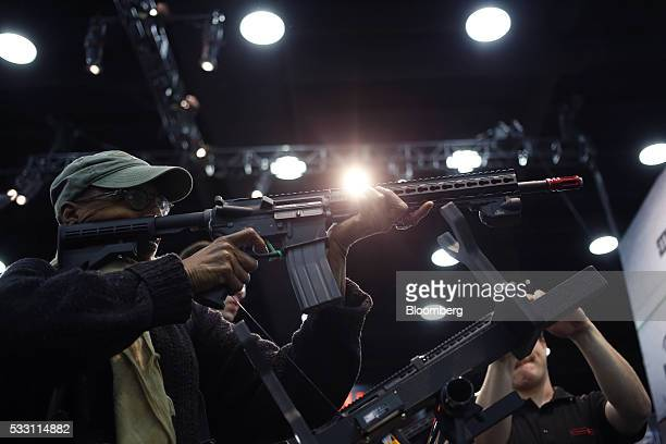 An attendee fires an AR15 style airgun during a laser simulation on the exhibit floor during the National Rifle Association annual meeting in...