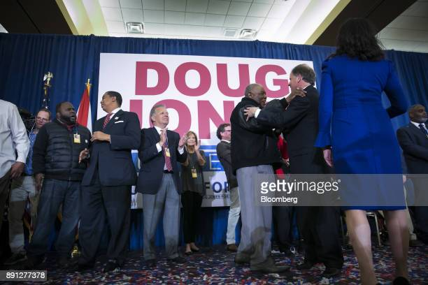 An attendee greets Senatorelect Doug Jones a Democrat from Alabama third right at an election night party in Birmingham Alabama US on Tuesday Dec 12...
