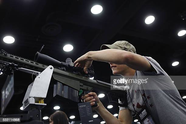 An attendee handles a Barrett Firearms Manufacturing 50 caliber sniper rifle on the exhibit floor during the National Rifle Association annual...