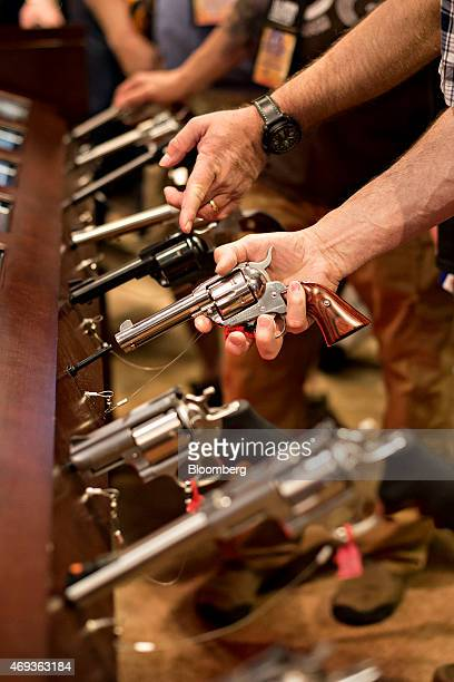 An attendee handles a revolver in the Sturm Ruger Co Inc booth on the exhibition floor of the 144th National Rifle Association Annual Meetings and...