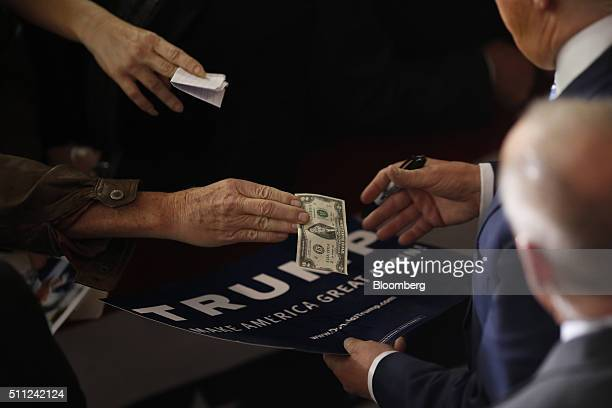 An attendee handles a US two dollar banknote to Donald Trump president and chief executive of Trump Organization Inc and 2016 Republican Presidential...