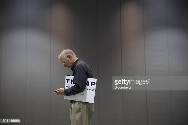 An attendee holding a campaign sign uses a smartphone as he enters a campaign event for Donald Trump president and chief executive of Trump...